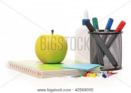 Office supplies - markers, exercise book and green apple isolated on white background