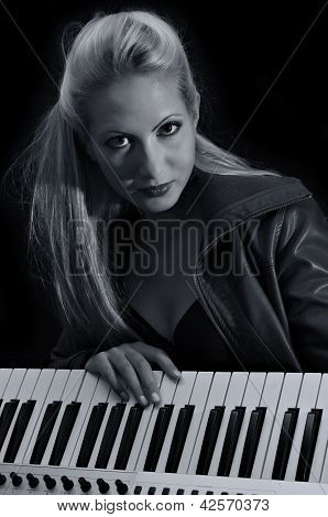 Sexy Lady In Bra And Leather Coat Posing With Synthesizer. Black And White