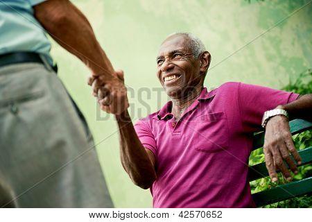 Reunión de hombres de negro y caucásico viejo y estrechar las manos en el Parque