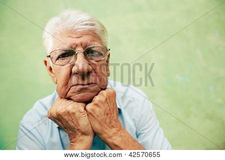 Retrato de homem velho sério, olhando para a câmera com as mãos no queixo