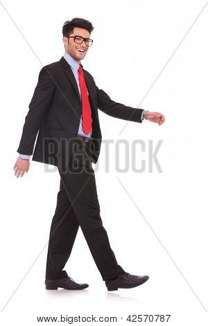 side view full length picture of a young business man walking and looking at the camera on white background