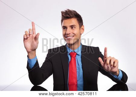 young business man sitting at his desk and pressing two imaginary buttons, with his look at one of them