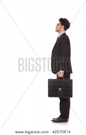 side view full length picture of a young business man standing with his suitcase in his hand and looking at something upwards, away from the camera at a 45 degree angle on white background