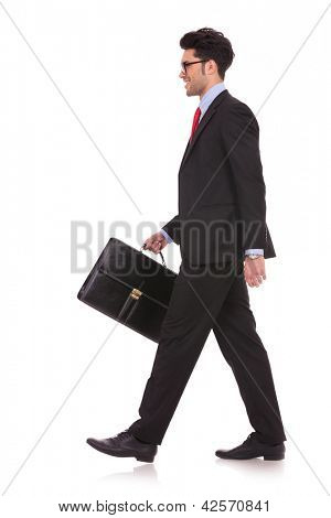 side view full length picture of a young business man walking forward with a briefcase in one of his hands and looking away from the camera on white background