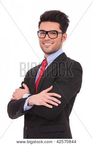 angle view of a young business man standing with his hands crossed and looking at the camera with a smile on his face, over white background
