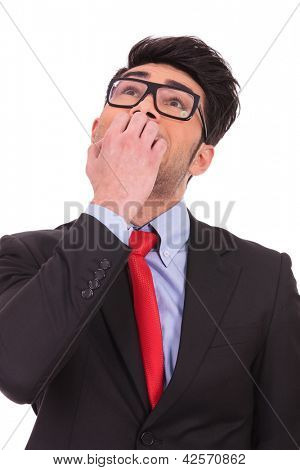 portrait of a scared young business man looking up, towards the sky, biting his nails, isolated on white