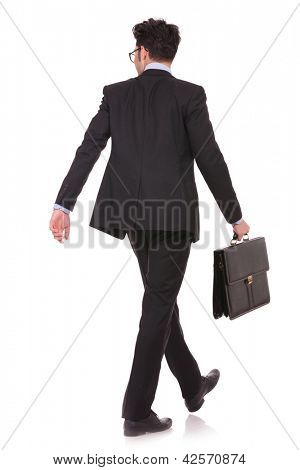 back view full length picture of a young business man walking with his suitcase and looking at something in a side direction on white background