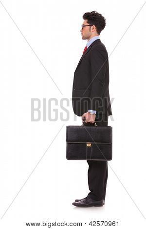 side view full length picture of a young business man standing with his suitcase in his hand and looking straight forward, away from the camera on white background