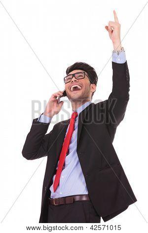 Retrato de un hombre joven hablando por teléfono y apuntando hacia arriba, mientras mira de