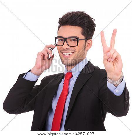 Closeup Retrato de un hombre de negocios joven hablando por teléfono y mostrando el signo de Victoria mientras sonriendo