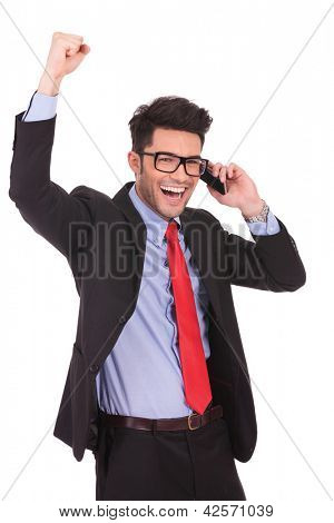 portrait of a young business man calling someone and celebrating, while looking away from the camera on a white background