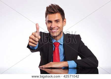 young business man at the table and showing thumbs up sign with a smile on his face while looking at the camera