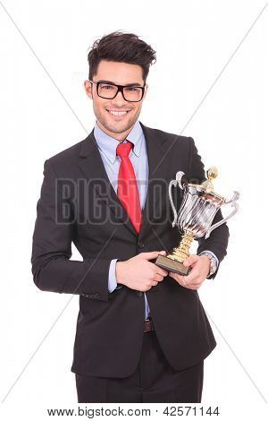 young business man holding a trophy and smiling to the camera, on white