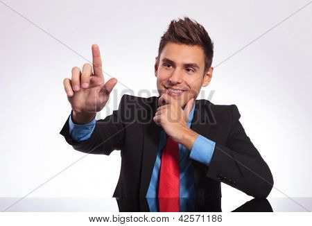 young business man sitting at the table and touching an imaginary button with his finger while pensively looking at it