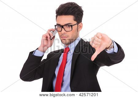picture of a young business man calling someone and showing thumb down gesture, while looking at the camera on a white background