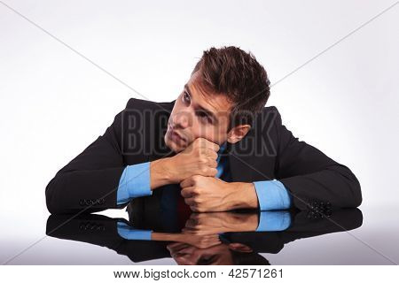 young pensive business man sitting at the desk with his fists supporting his head and looking away