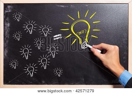 business man drawing many small light bulbs equal a big one. many ideas make a big one