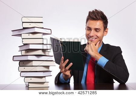 young business man at the office is reading an interesting book out of his stack, with a smile on his face