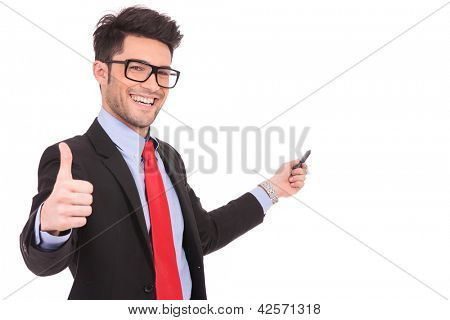 closeup portrait of a young business man showing thumbs up and pointing with a pen at something in the back, while smiling to the camera, on white