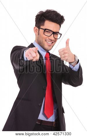young business man pointing towards the camera and showing thumbs up sign, on a white background