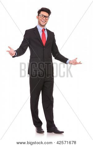 full length picture of a young business man welcoming everybody with his arms wide opened and with a large smile on his face, on white background