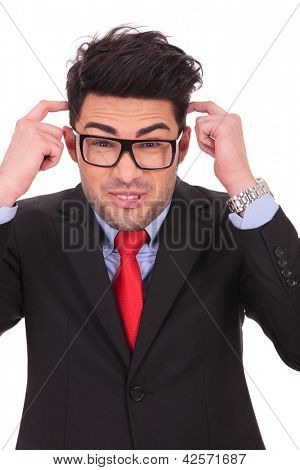 young business man scratching his head with both hands and making a funny face on a white background