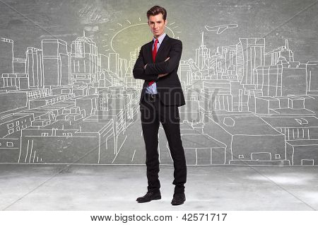 confident young business man standing in front of a sketch of a big city