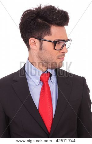 closeup portrait of a young business man looking doubtfully  at something from his side, on a white background