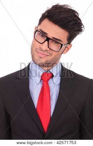 closeup portrait of a young business man with head tilted to a side is looking at the camera suspiciously, on a white background