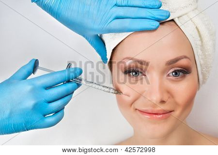 Young woman receiving a botox injection in her cheek