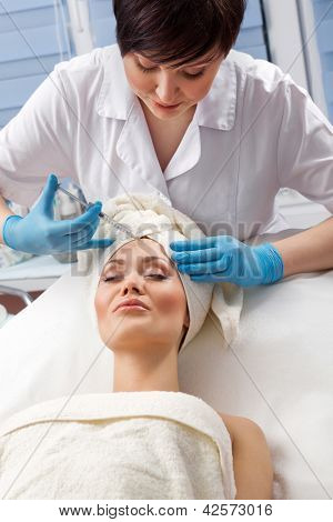 Young woman receiving a botox injection in her  forehead