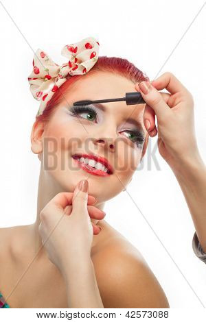 Backstage scene: Professional Make-up artist doing pinup model makeup at work