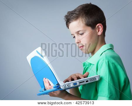 Young casual boy using a laptop against grey background