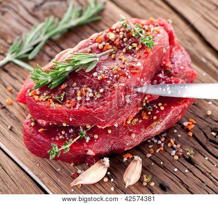 Raw beef steak on a dark wooden table.
