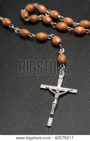 Rosary beads resting on a black leather bound bible