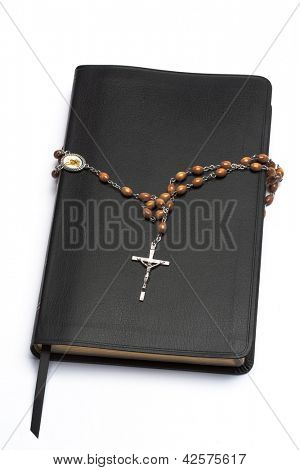 Rosary beads wrapped around the bible on white background