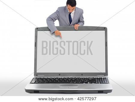 Businessman pointing down to blank laptop screen on white background