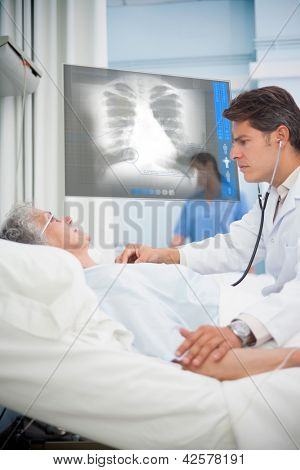 Doctor auscultating a patient with a stethoscope in hospital ward