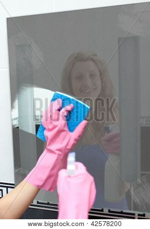 Glowing woman cleaning a mirror in a bathroom