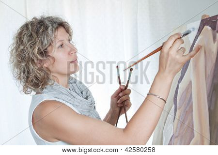Female Artist Painting A Picture. Against The Background The Studio.