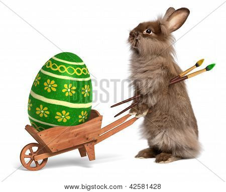 Funny Easter Bunny Rabbit With A Wheelbarrow And A Green Easter Egg