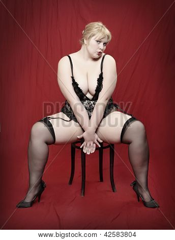 Retro style picture of the overweight woman dressed in black lingerie posing on a red background.