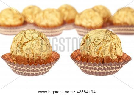 Group Chocolate Candies Wrapped In Gold. On A White Background.