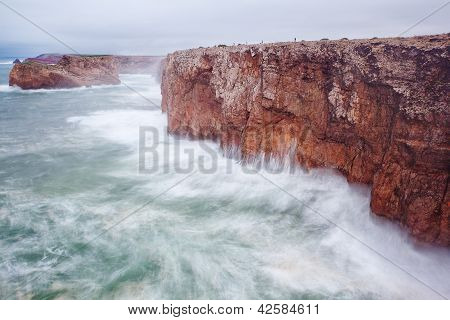 Small Fishermen On A Giant Rock In A Storm.