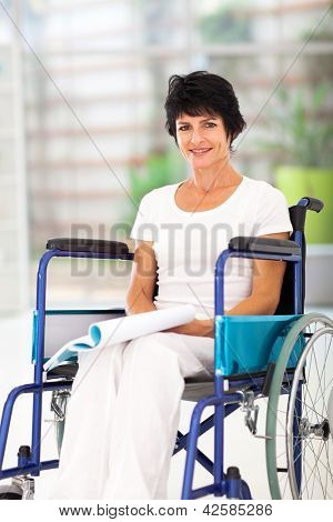 handicapped middle aged woman reading book on wheelchair