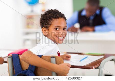 lindo colegial elemental, mirando hacia atrás en el aula