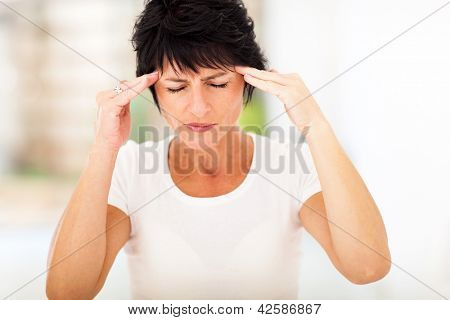 mid age woman having headache and massaging forehead