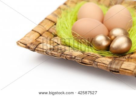 Brown and golden easter eggs are on wattled plate with sisal green fibre, isolated on a white background