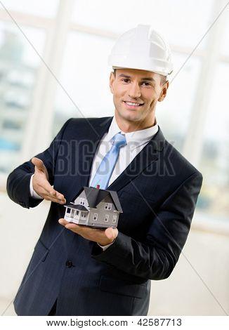 Konstruieren Sie in weißen Kopfstück auf kleines Modell Haus zeigen. Konzept der Immobilien