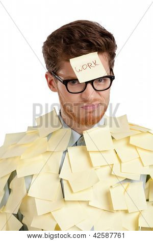 Young man with a sticky note on his face, covered with yellow sticky notes, isolated on white